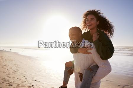 man giving woman piggyback on winter