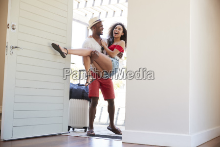man carries woman over threshold of