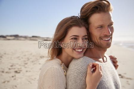 romantic couple embracing on winter beach