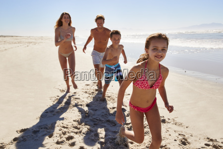 family on summer vacation running along