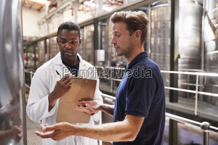 two men talk and inspect vats