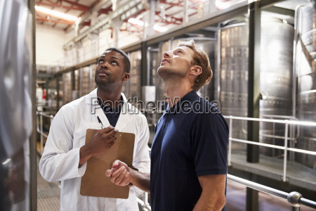 two men inspecting vats in a