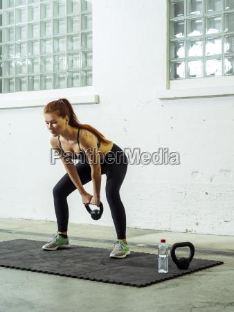 beautiful young redhead lifting kettlebell weights