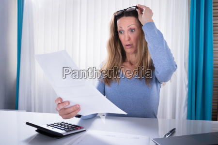 shocked woman looking at document in