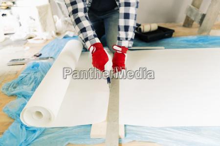 handyman worker measuring wallpaper to cut