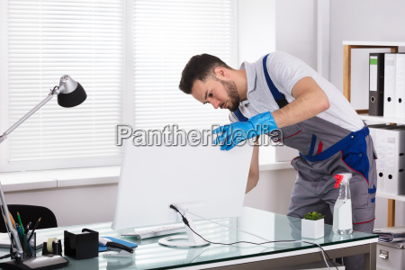 janitor cleaning computer in office