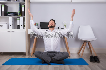 businessman raising his arms in office