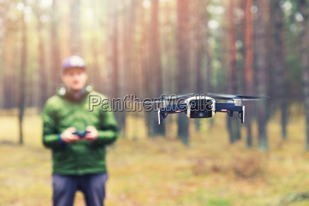 man flying drone in the woods