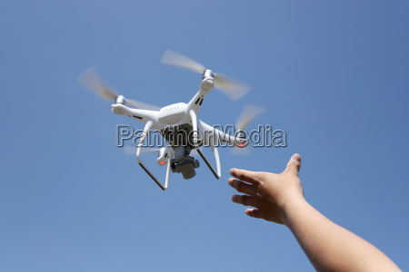 hand catching drone aircraft in blue