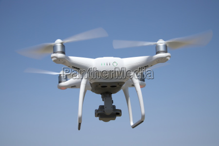 white drone flying in air and