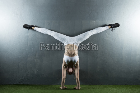 full length of woman practicing handstand