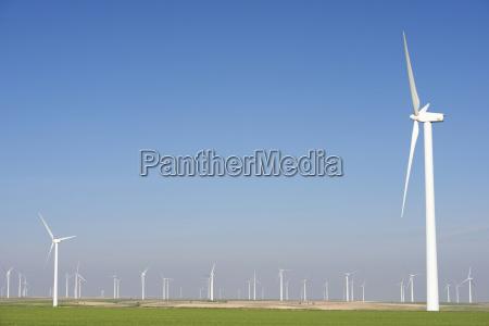 windmills on field against clear blue