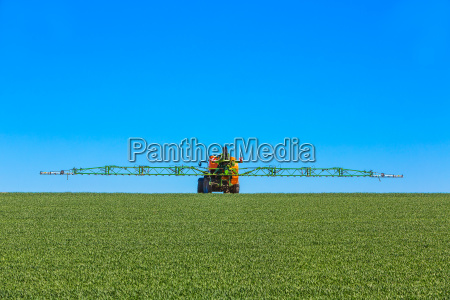 traktor besprueht junges feld mit glyphosat