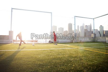 father playing soccer with man on