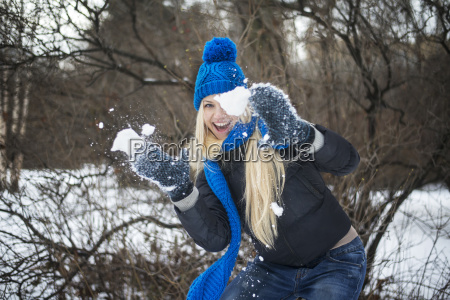 woman playing with snow on field