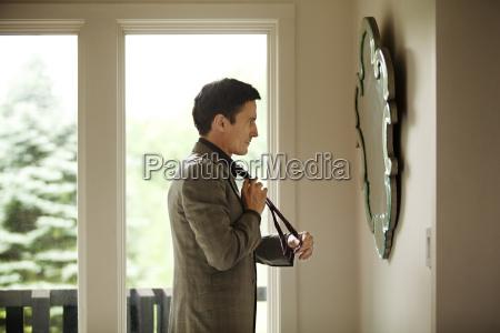 side view of man adjusting tie