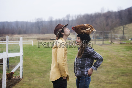 couple playing with chicken while standing