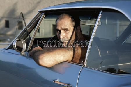 portrait of man looking through car