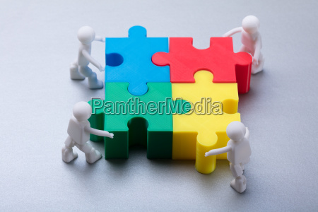 human figures solving jigsaw puzzle