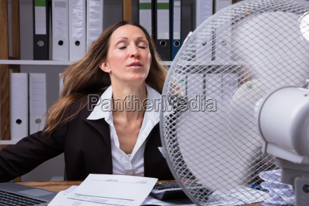 businesswoman cooling herself in front of