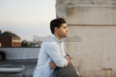 thoughtful man leaning on retaining wall