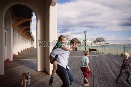 playful family on boardwalk outside building