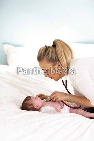 pediatrician examines baby with stethoscope at