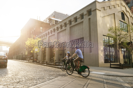 couple cycling on road by building