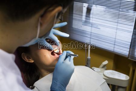 close up of dentist examining woman