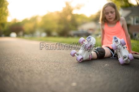 girl wearing roller skates sitting on