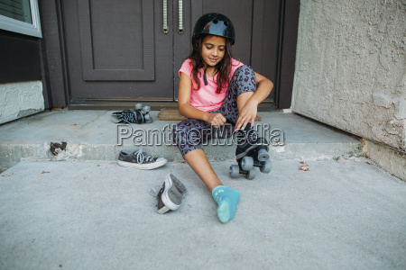 girl wearing roller skate while sitting