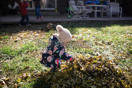 baby girl playing by heap of