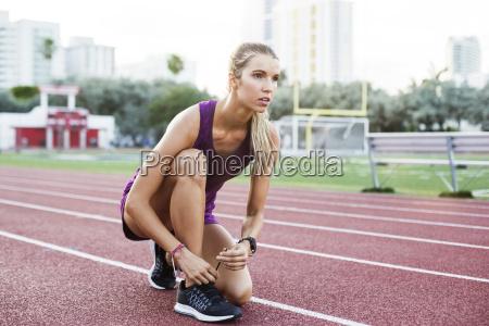 confident female athlete tying shoelace on