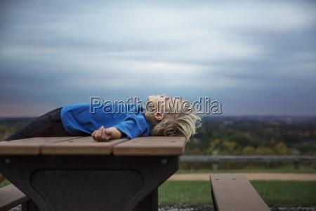 blonde, boy, lying, on, table, under - 24914834
