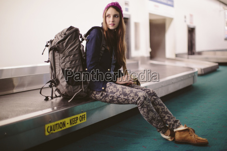 woman with luggage sitting on baggage