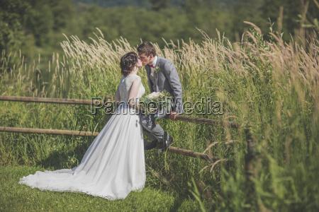 newlywed couple kissing at grassy field