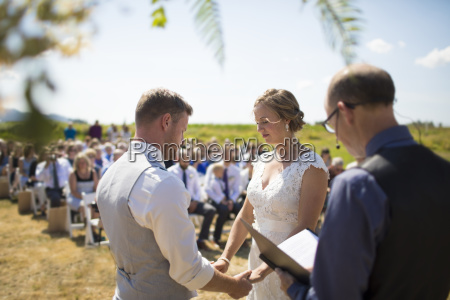 young couple getting married by priest