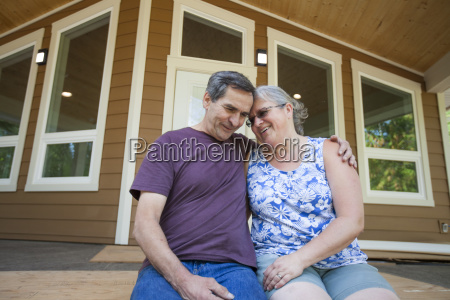 happy couple sitting against new house