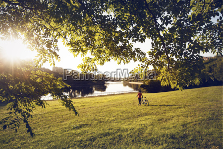 man with bicycle on grassy field