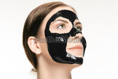 young beautiful woman applying a mask