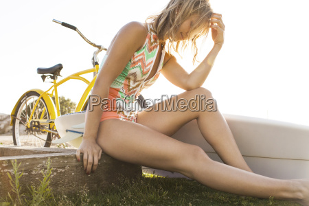 woman sitting with surfboard on beach