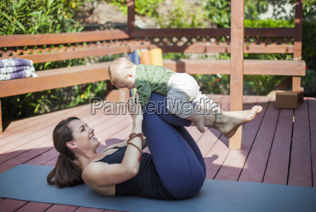 cheerful woman playing with baby while