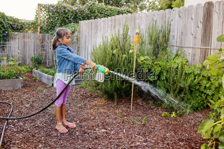 side view of girl watering plants