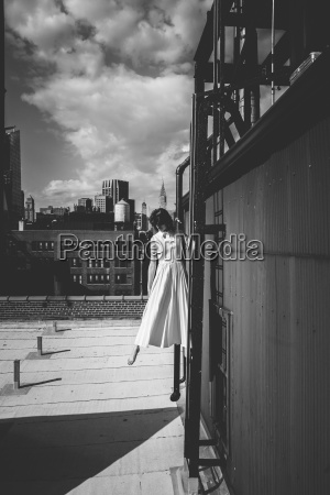 woman standing on ladder of building