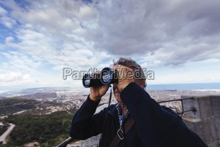 man using binoculars while standing against