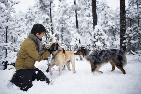 teenager playing with dogs against trees