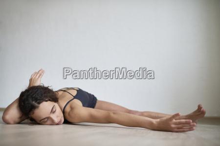 woman lying on hardwood floor while