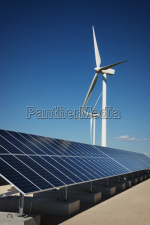 solar panels on factory by windmills