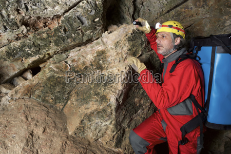 archaeologist with backpack standing in cave