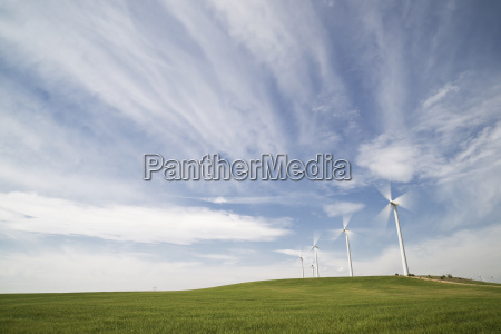 wind turbines on field against cloudy